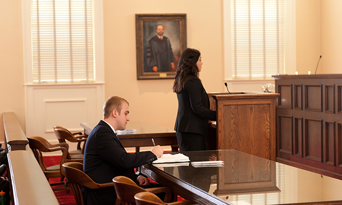 student speaking to judges during moot court competition