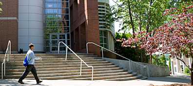 photo of man walking by steps and entrance to Dean Rusk Hall